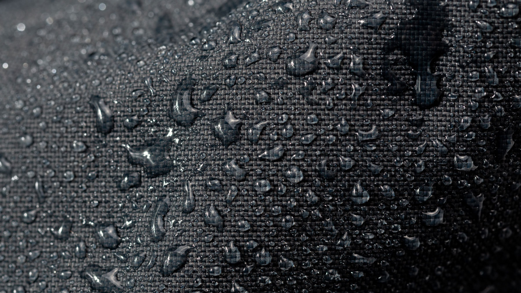 dark gray waterproof hydrophobic cloth closeup with water drops selective focus background