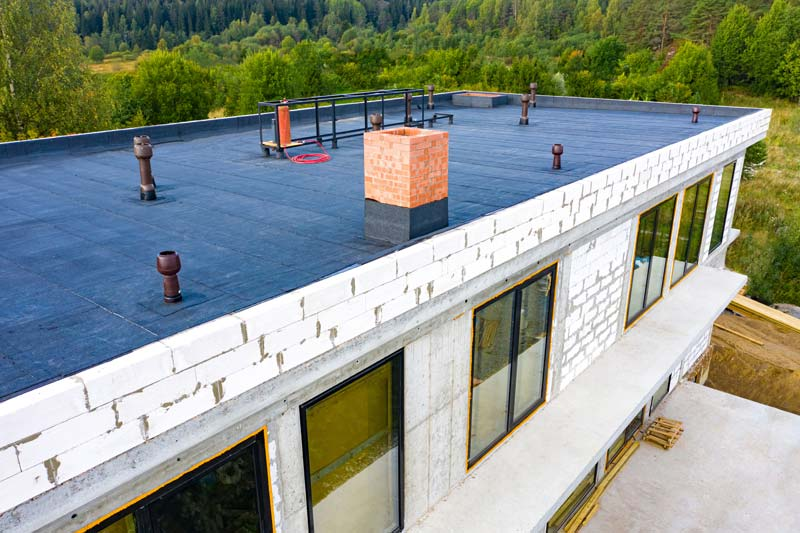 Roof waterproofing. Building construction. A protective layer was applied on the roof of the house. Installation of a waterproofing layer. Construction works. Bitumen insulating