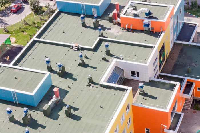 Top view flat roof with air conditioners and hydro insulation membranes on top of a modern blue and orange apartment building sunny summer day.